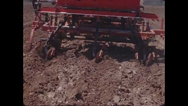 1960s: UNITED STATES: machinery creates rows in soil. Man on back of trailer in field