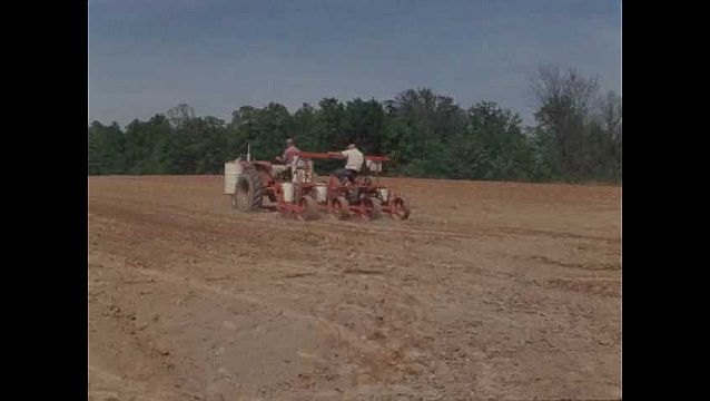 1960s: UNITED STATES: men on tractor plant seeds in field.