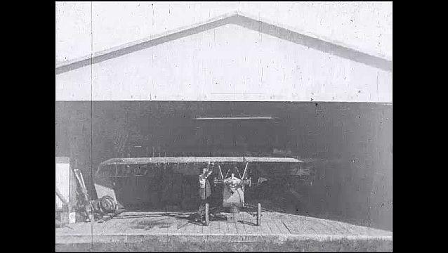 1920s: Garage, man in overalls inspects, walks around, works on glider, attaches support to wings, spins glider around, sets tail down.
