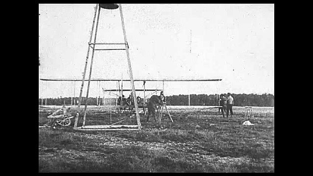 1920s: Man with camera records airplane on rail in field as weight drops from pully system propelling airplane down rail to flight. People in seats watch. Airplane flies.