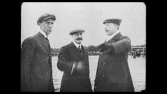 1920s: Three men stand talking then point in different directions.