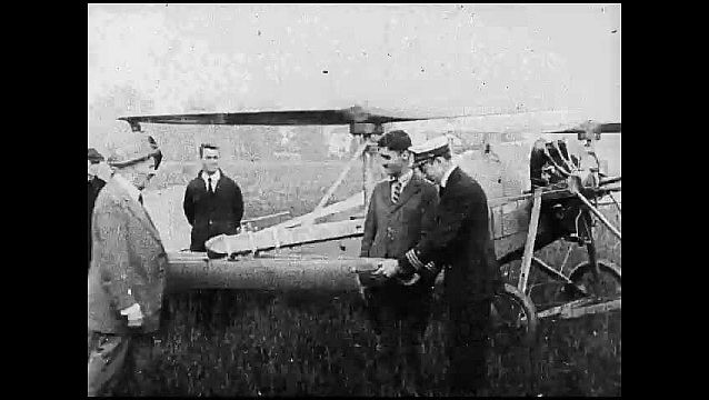 1920s: Men stand around early airplane with propellers facing upward like helicopter. Pilot tries lifting plane off ground but it keeps landing back down.