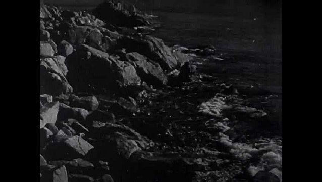 1940s: Rocky coast, waves roll in. Small bark wigwam huts, lawn. Robert Trent sits, weaves fishing net in lap.
