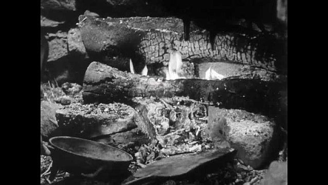 1940s: Dugout hut, man takes ashes out of fire with metal shovel, places in pan. Woman smiles, feeds boy lying in bed. Man walks into bark wigwam hut, man sits outside weaving fishing net.
