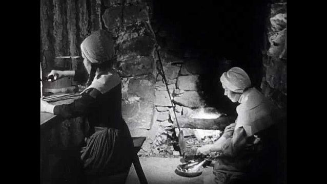 1940s: Hut, girl works at table splitting pitch pine splints for candles. Woman places fish in pan over fire. Man, boy walk past rocky hilltop, carry scythes.