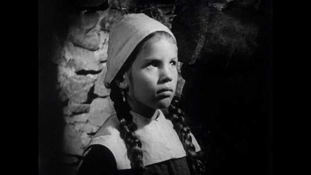 1940s: Hut, girl, boy look solemn, boy lies in bed sick. Rocky coast, waves roll in.