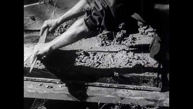 1940s: Brick works, man uses wooden board to scrape clay off brick mold. Open hut, blacksmith hammers nail on anvil, man operates bellows to fan fire.