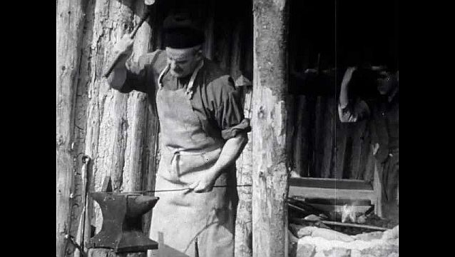 1940s: Open hut, blacksmith hammers nail on anvil, hits nail against blade, uses tool to break off nail from metal piece. Man operates bellows to fan fire.