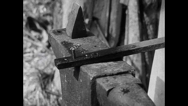 1940s: Blacksmith hammers nail through hole in metal piece to shape nail, nail falls onto pile. Men build thatched roof, man carries thatching material up ladder, hands to other man.