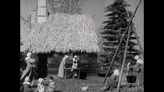 1940s: Busy village, thatched hut, people walk by, carry things, people work. Women make soap, tend kettle over fire, woman brings barrel over, woman pours liquid from barrel into kettle.