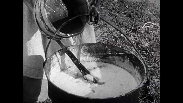 1940s: Women make soap, woman pours liquid from barrel into frothy kettle, stirs with wooden paddle. Field, man digs with hoe, places fish in hole, covers with soil, pulls corn seed from waist pouch.