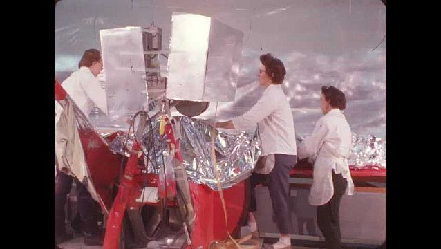 1960s: Three women in white lab coats, unfold and smooth thin metallic sheet in brightly lit room.