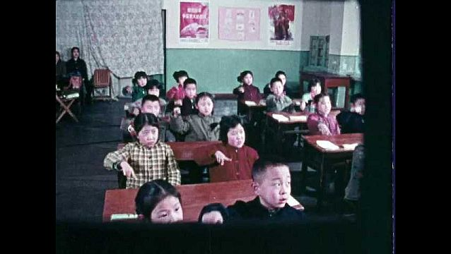 1960s: Students sit in desks, speak, move fingers through air. Woman stands at chalkboard. Boy uses abacus.