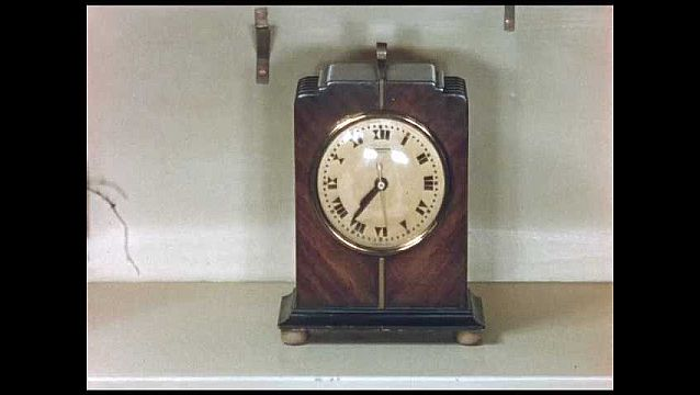 1950s: wooden antique clock, teal fan blowing, model train drives around track, the end