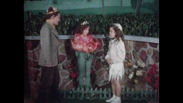 1960s: Boy talks to girl in rose costume. Other girl talks, leaves. Girl in rose costume talks to boy.