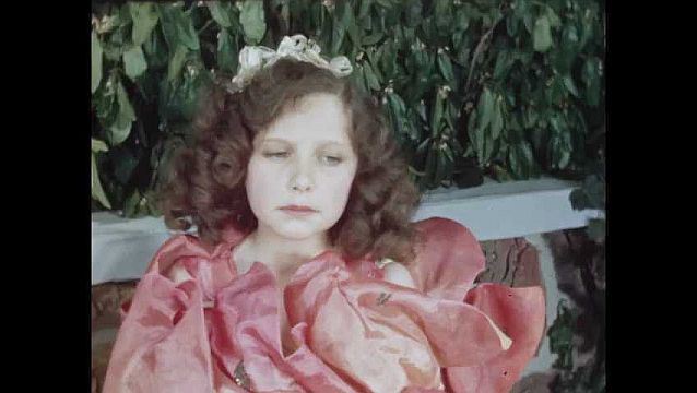 1960s: Boy talks to girl in rose costume. Young boy approaches, upset, sits on bench. Boy talks to young boy.