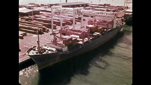 1970s: Cargo ship sits at port under cranes. Crane lifts and carriers shipping container. Title on screen. Crane lowers container onto dock.