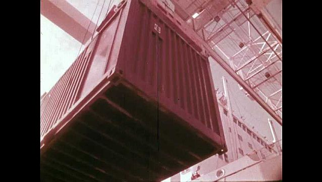 1970s: Cranes lower shipping containers. Hands move on clock. Wheels turn and plane moves on strip. Shipping containers lower on cranes. Cargo ships at port.