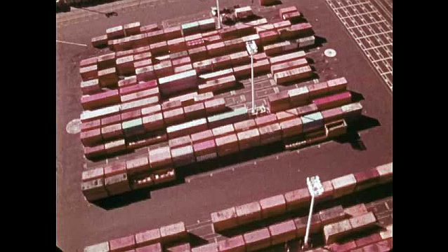 1970s: Aerial footage of shipping containers and truck trailers at port.