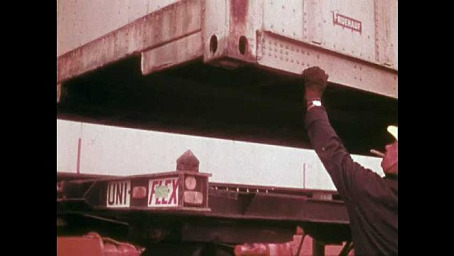 1970s: Men help crane to position shipping container onto truck bed, Man drives truck away from crane. Crane lowers shipping container onto bed of truck. Men position container onto truck.
