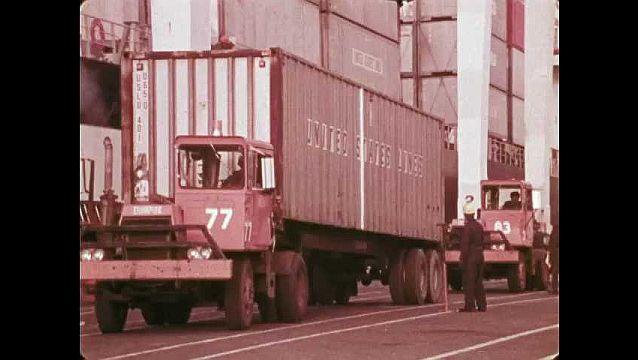 1970s: Trucks drive from port crane onto access road. Trucks drive on overpass over railroad tracks.