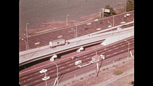 1970s: Trucks and cars drives on highway overpass. Truck drives on highway Traffic on highway. Cars and trucks drive on interstate by Oakland.