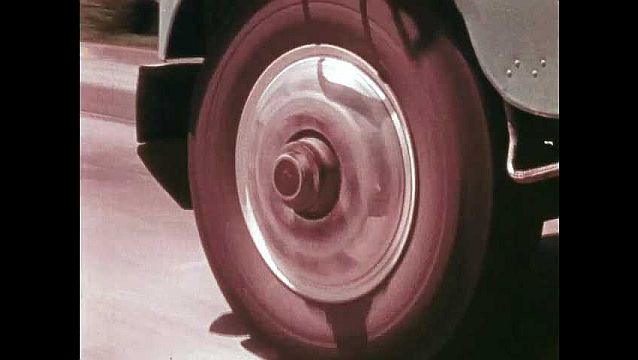 1970s: Truck wheels spin on highway. Interstate sign on overpass. Trucks drive on interstate.