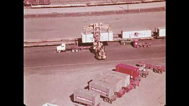1970s: Lift truck holds shipping container above truck. Truck pulls away. Lift vehicle lowers shipping container onto train car. Man waves baton and directs trucks in rail yard.
