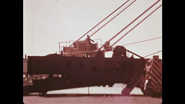 1970s: Forklifts and lift vehicles drive across ramp and onto cargo ships. Crane lifts palettes of goods from cargo ship.