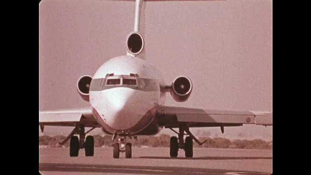1970s: Commercial airplane taxis on runway. Men load shipping containers onto airplane with conveyor ramp. Containers roll past airplane on runway.