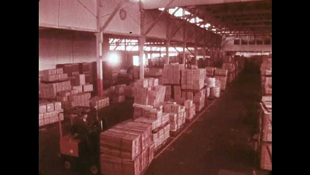 1970s: Forklift moves palette of boxes through large warehouse.