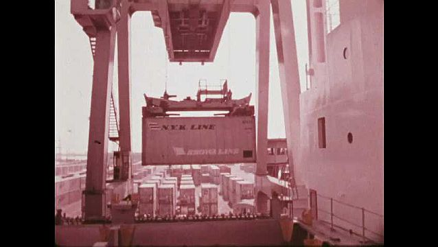 1970s: Cranes lift and move shipping containers onto ships at Port of Oakland. Crane lowers container into cargo hold. Computer monitor. Crane moves container onto cargo ship.