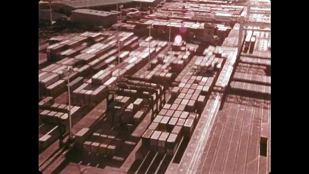 1970s: Aerial view of shipping containers and cranes at Oakland Port. Aerial view of cargo ship at port.