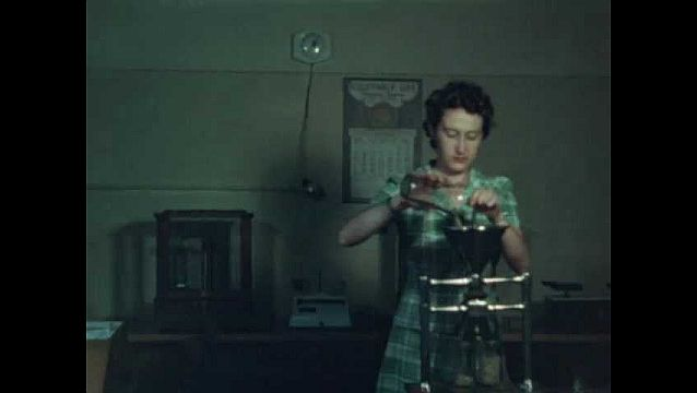 1940s: UNITED STATES: lady uses grinder in room. Weeds in garden