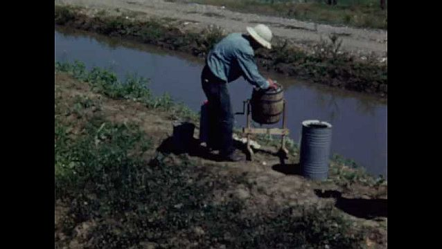 1940s: UNITED STATES: men mix up weed killer in mixer. Man sprays weeds by water. Man pushes weed killer machine across ground