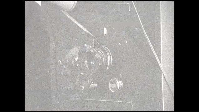 1950s: View of camera lens, light shining. Light shines on photo in glass frame. Man developing photograph.