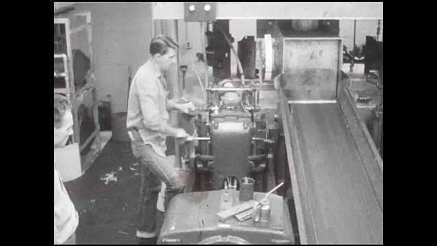 1950s: Man removes paper from machine, other man adjusts machine. Man moves machine parts.
