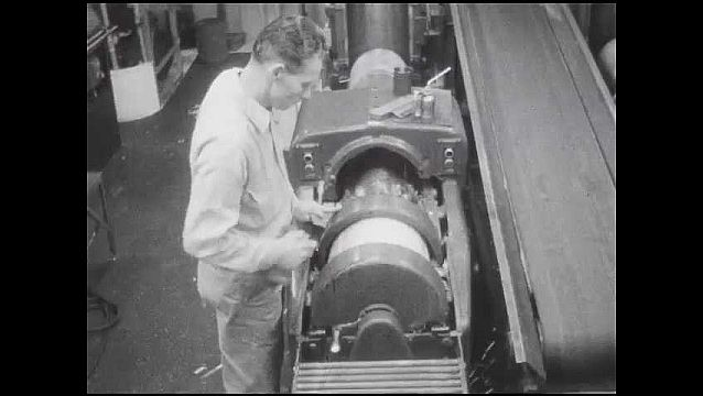 1950s: Man moving machine parts. Plate sliding on conveyor belt. Mna puts plate on roller in printing press, presses button.