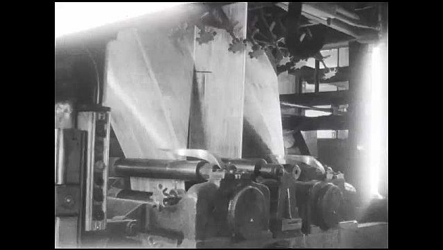 1950s: Paper running though printing press. Tilt up, newspaper carried through machine in warehouse. Tilt down, machine moving papers, men stacking papers.