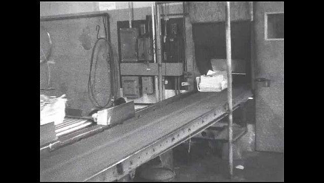 1950s: Stacks on newspaper on conveyor belt. Newspapers drop onto belt. Men load newspapers into truck.