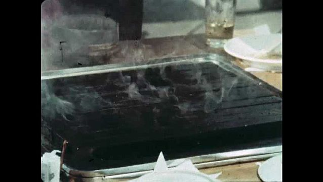 1960s: Smoke rises from grill. Server places raw meat on grill with chopsticks. Meat and vegetables sizzle on hot grill.