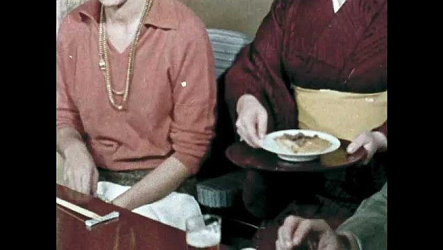 1960s: Server places sukiyaki before woman. Woman dips meat into raw egg and eats. Woman eats and speaks to guests.