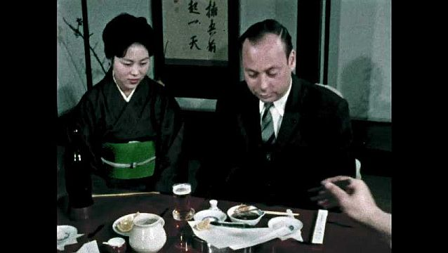 1960s: Chef places tempura on man's plate. Server squeezes lime on tempura. Man dips tempura into bowl of sauce.