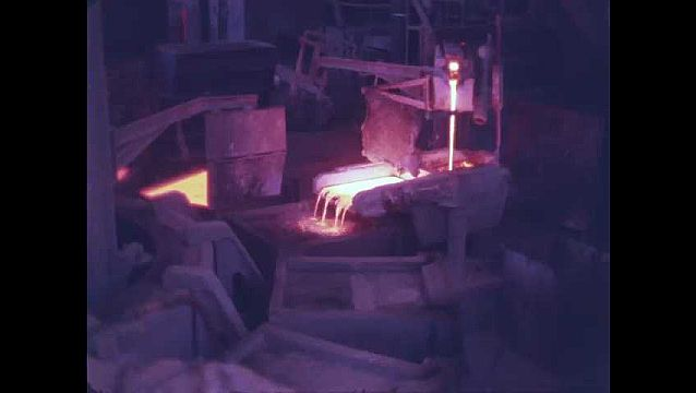 1950s: Smoke and molten metal pour from forge. Sparks fly from vat of molten metal. Glowing metal rolls along conveyor belt in mill.