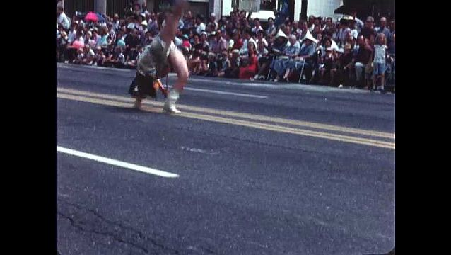 1950s: UNITED STATES: lady with baton in carnival. Lady in street parade. Majorette performs somersault in street