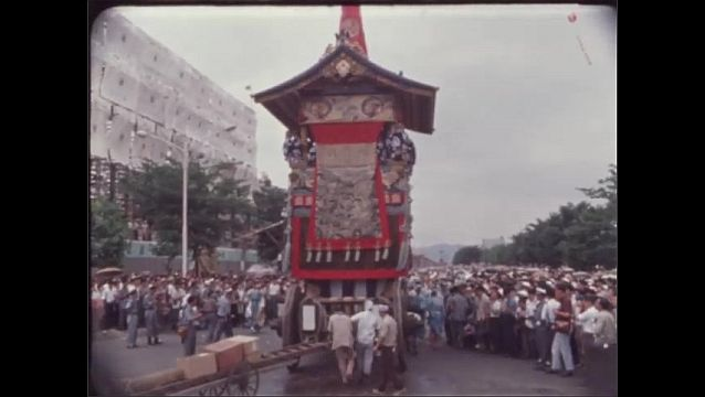 1960s JAPAN: Men lean from tower float. Garlands and charms hang from spire of tower float. Men pull ropes and guide Yamaboko Junkō tower in parade. Men throw items from tower to crowd.