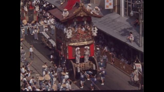 1960s JAPAN: Men wave fans and ride on large tower floats in parade. Banners wave from buildings. Men adjust cameras and talk.
