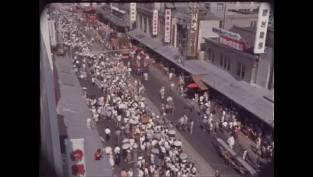 1960s JAPAN: Men use wet bamboo and ropes to turn float. Men push large tower floats in parade. Cars and street cars roll down crowded Kyoto street. Crowds walk past paper lanterns.