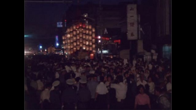 1960s JAPAN: Crowds walk through streets of Kyoto. Crowds walk past paper lanterns at end of Gion Festival. Title placard.