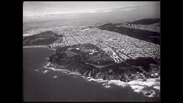 1940s: Aerial view of San Francisco city, street grid, coastline, cliffs, waves, Pacific Ocean.